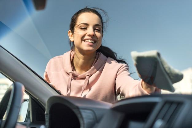 Frau, die die vordere windschutzscheibe an ihrem auto reinigt