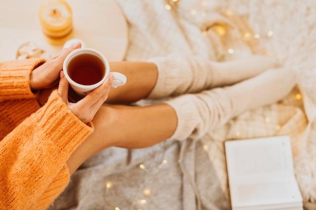 Frau, die die winterferien mit einer tasse tee genießt