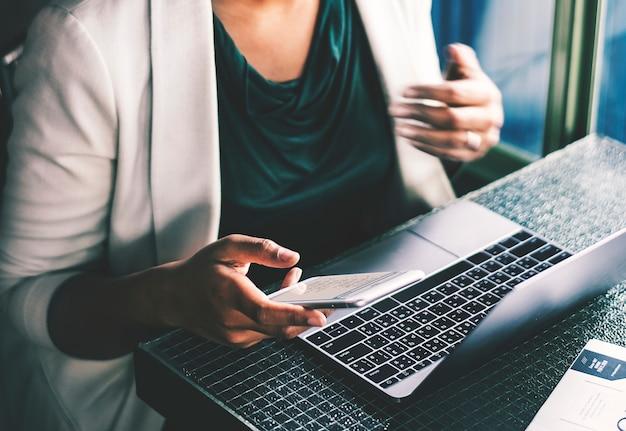 Frau, die digitale geräte am café verwendet
