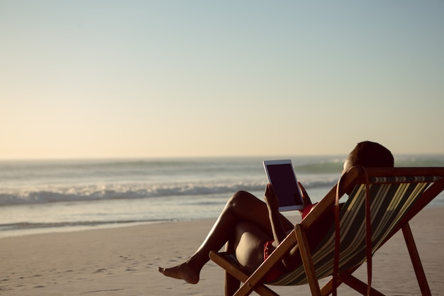 Frau, die digitale tablette bei der entspannung in einem strandstuhl auf dem strand verwendet