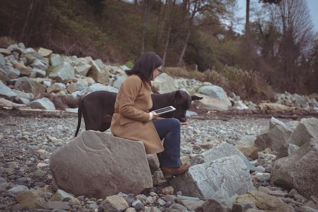 Frau, die digitale tablette durch hund am strand hält