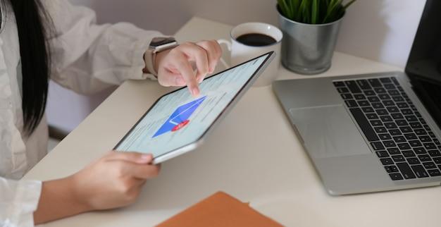 Frau, die digitale tablette für den e-mail-kasten überprüft im büro verwendet