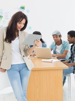 Frau, die digitale tablette mit kollegen hinten im büro verwendet