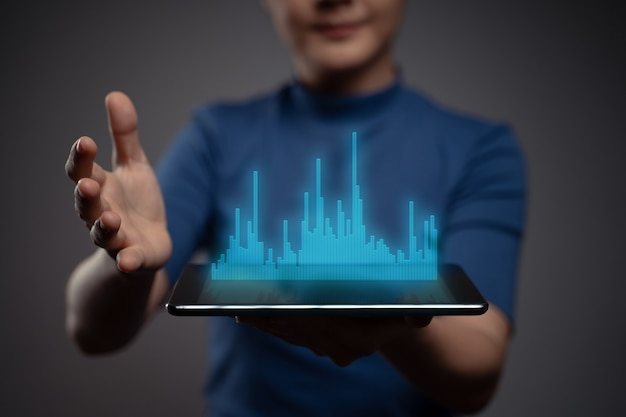 Frau, die digitales marketing der tablettplanung mit diagrammhologrammeffekt verwendet