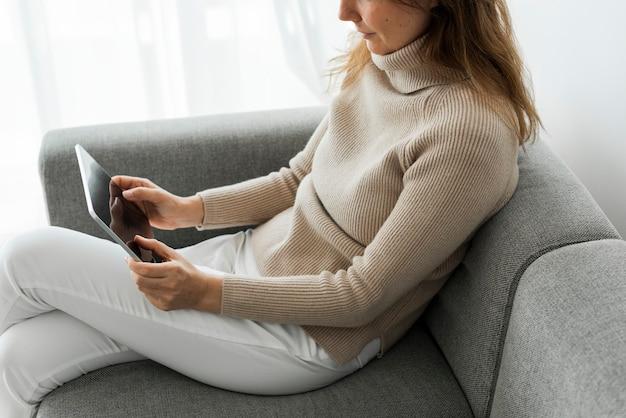 Frau, die digitales tablett auf einer couch verwendet