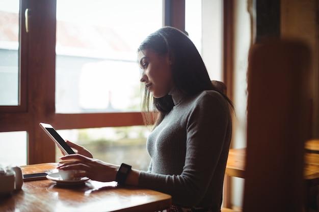 Frau, die digitales tablett beim kaffeetassen verwendet