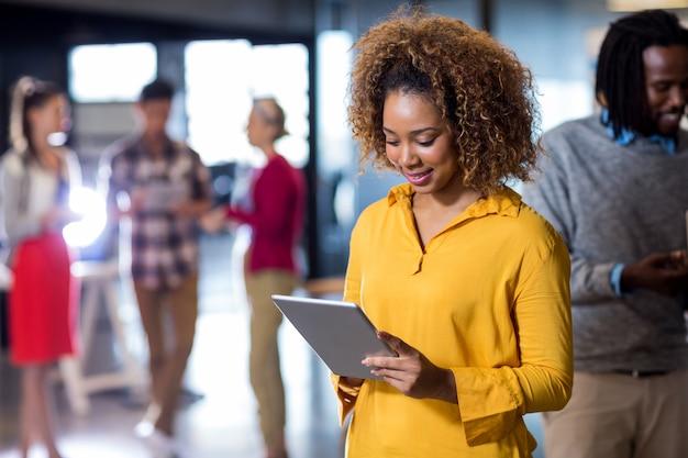 Frau, die digitales tablett im büro verwendet