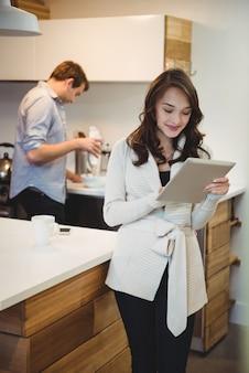 Frau, die digitales tablett verwendet, während mann im hintergrund arbeitet