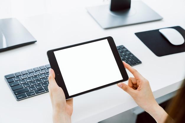Frau, die digitales tablettenmodell des leeren bildschirms und des computers auf tischbüro hält.