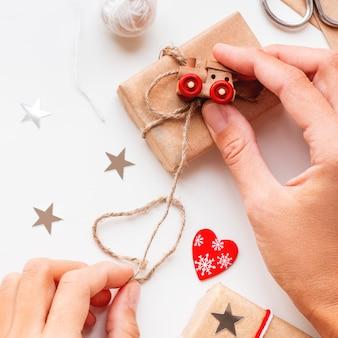 Frau, die diy-geschenke im kraftpapier einwickelt. geschenke mit weißen und roten fäden mit spielzeugeisenbahn als dekoration gebunden.