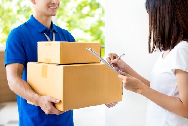 Frau, die dokument unterschreibt und paketbox vom zusteller erhält