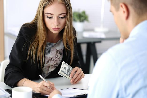 Frau, die dokumente unterschreibt, nachdem sie eine charge von handred dollarnoten erhalten hat. venalität, bestechung, korruptionskonzept