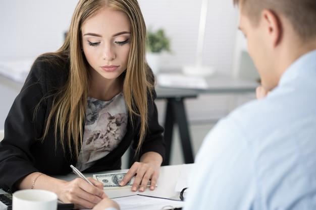 Frau, die dokumente unterschreibt, nachdem sie einen stapel von hundert dollar-scheinen erhalten hat. venalität, bestechung, korruptionskonzept