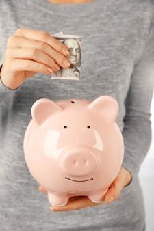 Frau, die dollarbanknote in ein sparschwein setzt. finanzsparkonzept