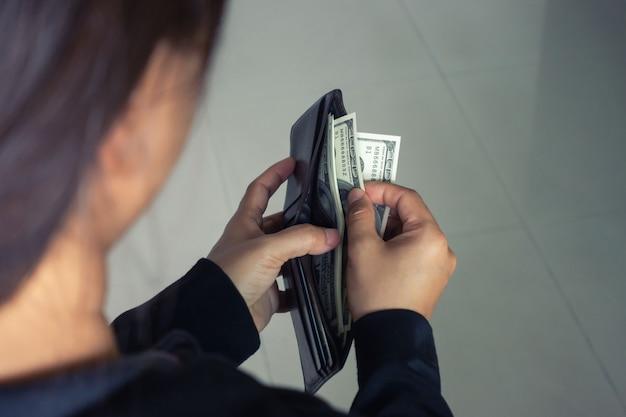 Frau, die dollarbanknoten von der geldbörse herausnimmt