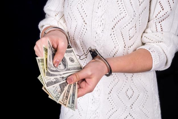 Frau, die dollarnoten in handschellen hält