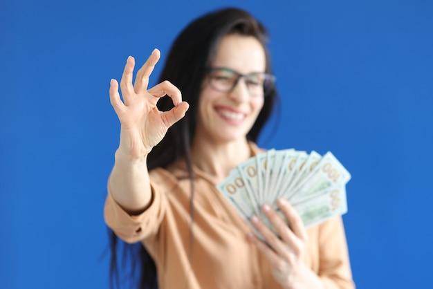 Frau, die dollarnoten in ihren händen hält und ok geste nahaufnahme zeigt