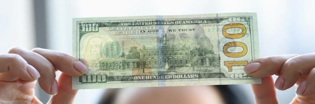 Frau, die dollarschein hält und es mit wasserzeichen nahaufnahme betrachtet. fälschungsgeldkonzept