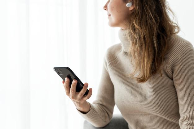Frau, die drahtlose ohrhörer trägt und ein mobiltelefon verwendet