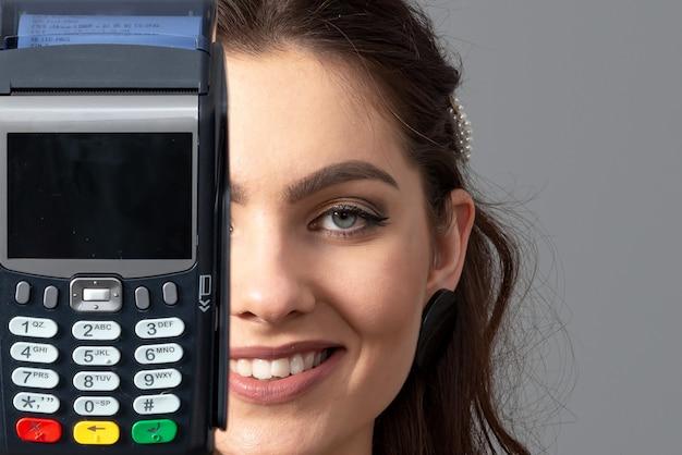 Frau, die drahtloses modernes bankzahlungsterminal hält, um kreditkartenzahlungen zu verarbeiten und zu erwerben