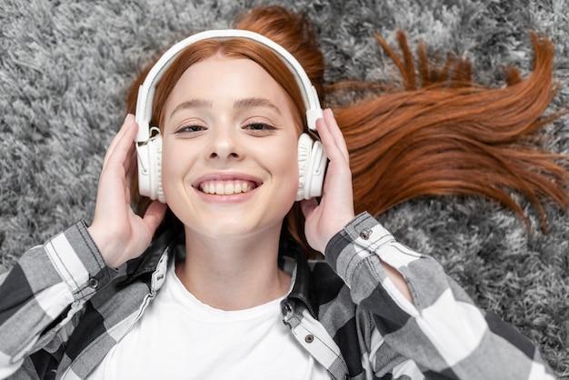 Frau, die draufsicht der musik genießt