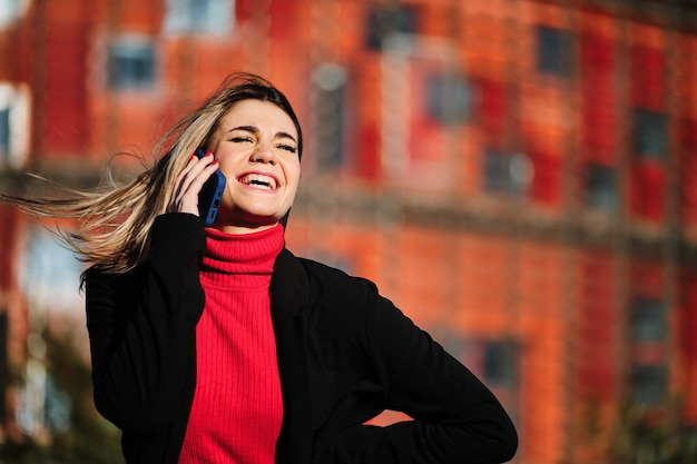 Frau, die draußen am telefon spricht.