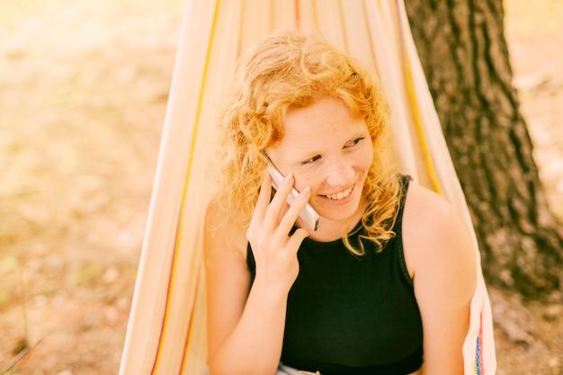Frau, die draußen am telefon spricht