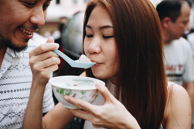 Frau, die draußen asiatischen nachtisch isst