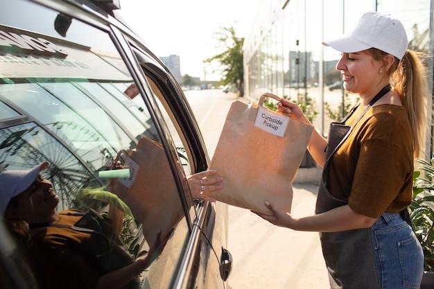 Frau, die draußen bei einer abholung am straßenrand eine bestellung aufgibt