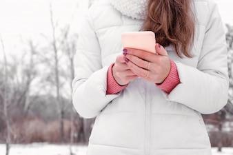 Frau, die draußen des weißen rosafarbenen Social Social Bloggers des Mantels rosa verwendet