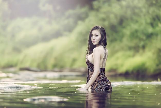 Frau, die draußen dusche in tropischem grünem bali-garten mit vielen blumen nimmt