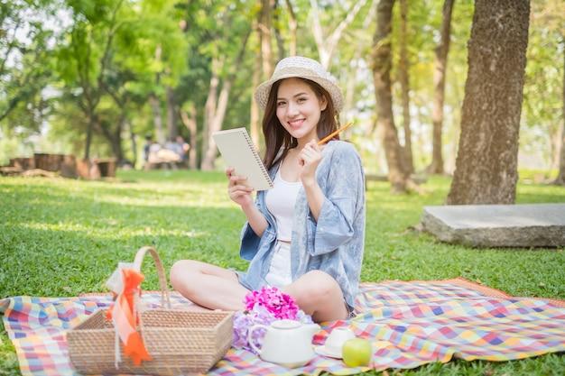 Frau, die draußen eine entspannende picknickmittagessenpause hat