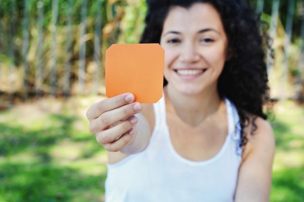 Frau, die draußen einen leeren notizblock zeigt.