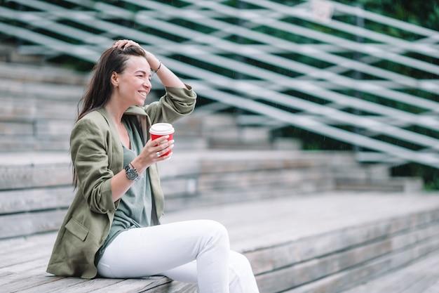Frau, die draußen geschmackvollen kaffee im park trinkt