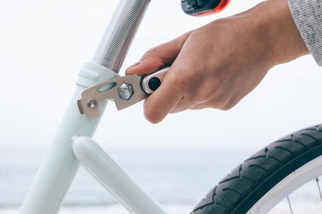 Frau, die draußen ihr fahrrad repariert