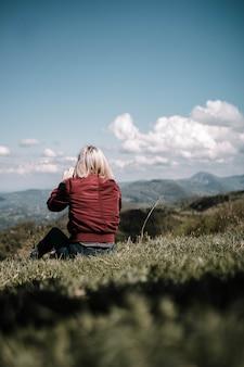 Frau, die draußen in einem schönen feld in der landschaft sitzt