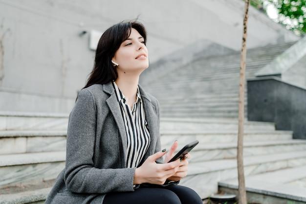 Frau, die draußen telefon und drahtlose ohrhülsen verwendet