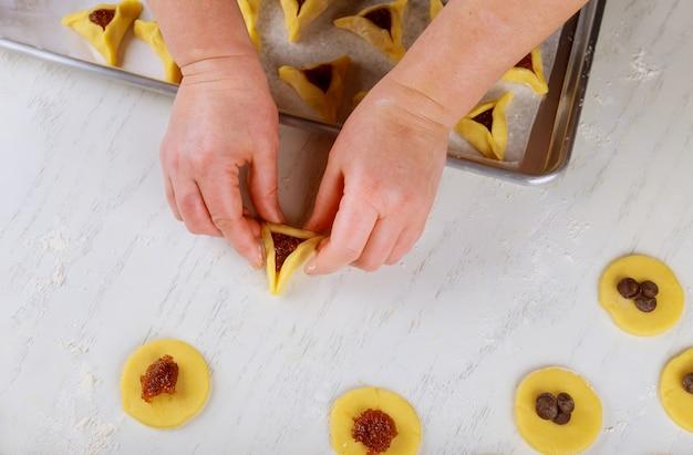 Frau, die dreieckigen keks für jüdischen feiertag purim macht.