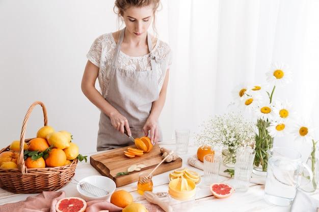 Frau, die drinnen steht, schneidet die orange. zur seite schauen.