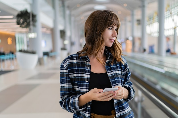 Frau, die durch den flughafen mit ihrem smartphone-gerät geht.