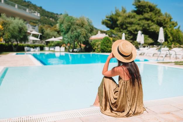 Frau, die durch den pool in einem luxushotelerholungsort genießt perfekte strandurlaubferien sich entspannt