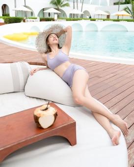 Frau, die durch den pool mit kokosnüssen, sommerferien entspannt.