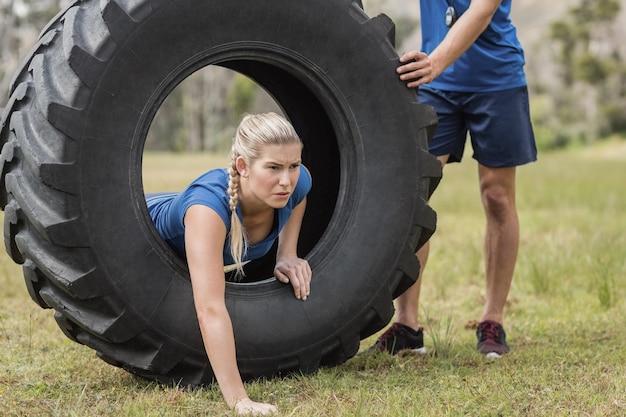 Frau, die durch den reifen während des hindernislaufs im bootcamp kriecht