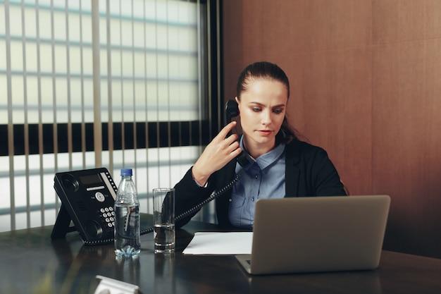 Frau, die durch die tabelle mit laptop im büro sitzt