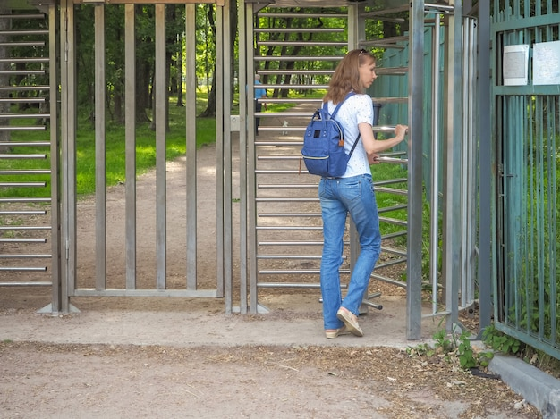 Frau, die durch ein drehkreuz zu einem privaten park geht