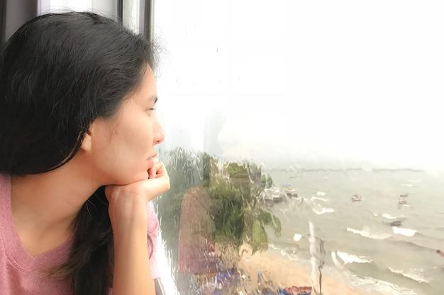 Frau, die durch ein fenster an einem regnerischen tag schaut