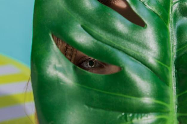 Frau, die durch grünes blatt schaut