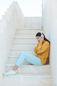 Frau, die durch hörende musik mit den kopfhörern sitzen auf schritten sich entspannt