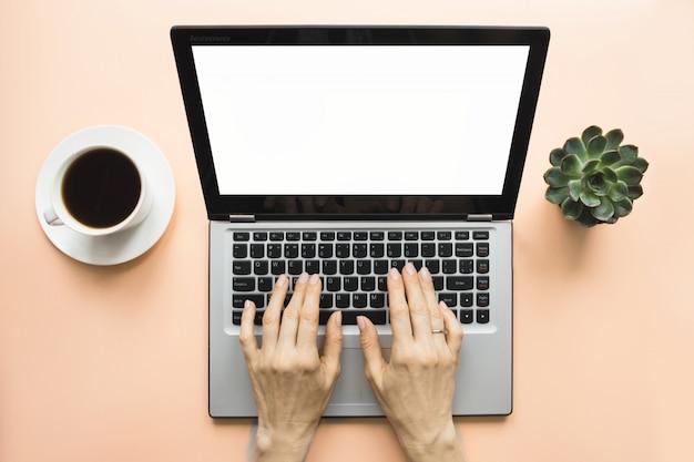 Frau, die durch laptop auf bürorosatabelle schreibt. platz für text auf dem bildschirm.