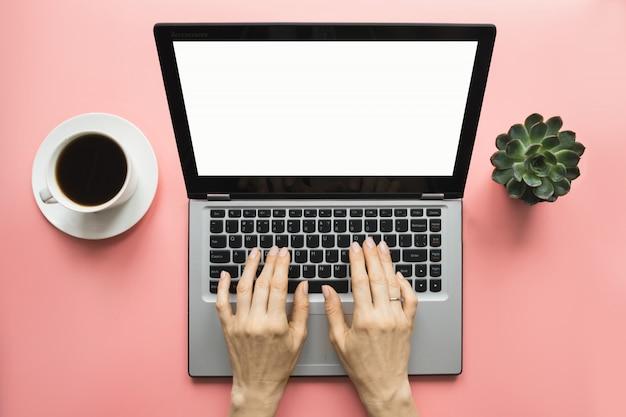 Frau, die durch laptop auf der rosatabelle des büros schreibt. platz für text auf dem bildschirm.